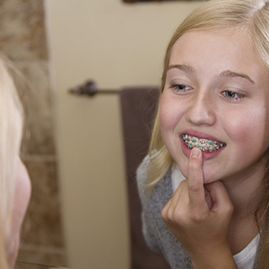Girl examining her braces in the mirror