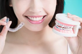Woman holding braces and a clear tray in each hand